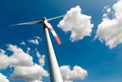 Wind turbine and couds. Low angle view of a wind turbine against a blue sky full of white clouds Royalty Free Stock Images