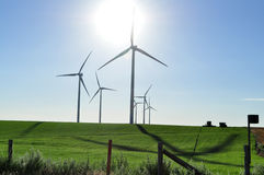 Wind turbine creating wind power. Modern windmills or wind turbines turn and create kinetic energy which is converted into electricty or renewable energy on Stock Images