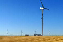 Wind turbine creating wind power. Modern windmills or wind turbines turn and create kinetic energy which is converted into electricty or renewable energy on Stock Photo