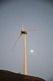 Wind turbine during dusk with moon behind Royalty Free Stock Photo
