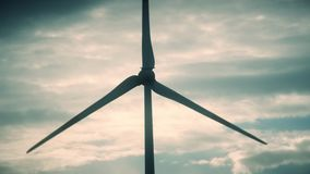 Wind turbine electricity generator blades spin on cloudy sky background. Wind turbine electricity generator blades spin on dark cloudy sky background Static shot stock video footage