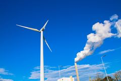 Wind turbine and factory chimney Stock Photo