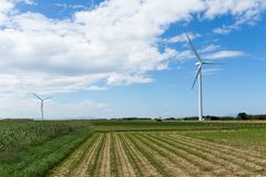 Wind turbine and farm with blue sky Stock Images