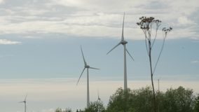 Wind turbine farm, electric power generators, on field on cloudy sky background. stock video