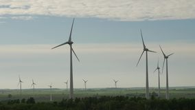 Wind turbine farm, electric power generators, on field on cloudy sky background. stock footage