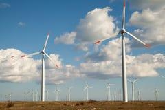 Wind turbine farm. Over the blue clouded sky Stock Photos