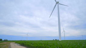 Wind turbine farm. Rural road between two farm fields with wind turbines. Panning from old road to wind turbine on background of cloudy sky. Corn field with stock footage
