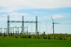Wind turbine farm and substation electricity power line in landscape with green grass and blue sky. Stock Photos