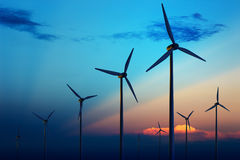 Wind turbine farm at sunset. Wind turbine farm with rays of light at sunset stock photos