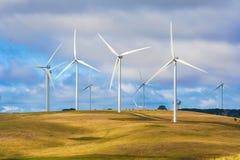 Wind turbine farm windmills creating energy on top of hill Stock Images