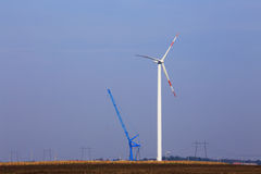 Wind turbine in the field beside crane. Royalty Free Stock Images