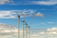 Wind turbine generating electricity on blue sky with clounds,Windmills for electric power ecology concept stock images