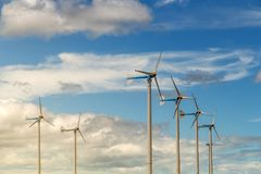 Wind turbine generating electricity on blue sky with clounds,Windmills for electric power ecology concept stock photography