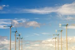Wind turbine generating electricity on blue sky with clounds,Windmills for electric power ecology concept stock photo