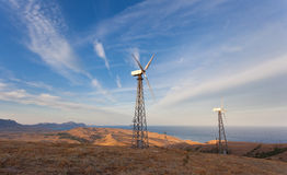 Wind turbine generating electricity in mountains at sunset.  royalty free stock photo