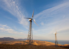 Wind turbine generating electricity in mountains at sunset.  stock images