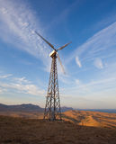 Wind turbine generating electricity in mountains at sunset.  royalty free stock image