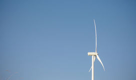 Wind turbine generating electricity over blue sky Stock Images