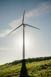 Wind turbine generating electricity over blue sky Royalty Free Stock Image