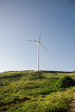 Wind turbine generating electricity over blue sky Royalty Free Stock Photography