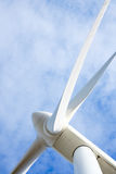 Wind turbine generator. View with blades spinning around under a beautiful dark blue cloudy sky royalty free stock images