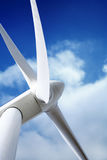 Wind turbine generator. View with blades spinning around under a beautiful dark blue cloudy sky stock image