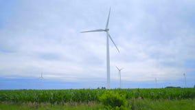 Wind turbine generator on green farm field. Road sign pointing on wind turbines stock video footage