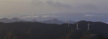 Wind turbine generator on mountain panorama. Wind turbine generator on high mountain,shoot with morning fog at sunrise Royalty Free Stock Images