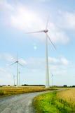 Wind turbine generators in a field against  sky. Wind turbine generators in a field against blue sky Stock Photography