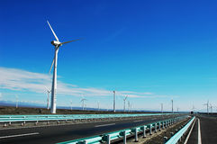Wind turbine generators by a highway Royalty Free Stock Photography