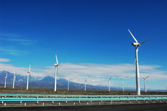 Wind turbine generators by a highway. In sinkiang,china,with blue skies and white clouds as a background Royalty Free Stock Images
