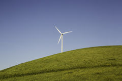 Wind Turbine. On a grassy hill on a clear day Royalty Free Stock Photography