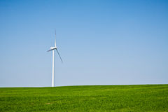 Wind turbine on green field royalty free stock image