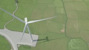Wind turbine on green field aerial view. Wind power turbine generation on energy station drone view from above. Alternative energy sources, ecology and stock footage