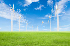 Wind turbine on green grass with blue sky Royalty Free Stock Images
