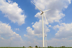 Wind turbine on the green grass over the blue clouded sky Stock Images