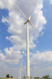 Wind turbine on the green grass over the blue clouded sky Royalty Free Stock Photos