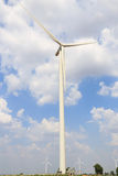 Wind turbine on the green grass over the blue clouded sky Stock Photos