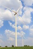 Wind turbine on the green grass over the blue clouded sky Royalty Free Stock Photography