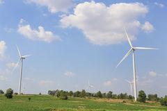 Wind turbine on the green grass over the blue clouded sky Stock Image