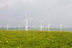 Wind turbine on the green grass over the blue sky Royalty Free Stock Photo