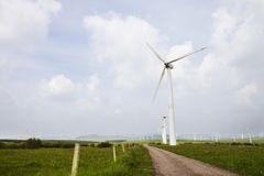 Wind turbine on the green grass over the sky Royalty Free Stock Photos