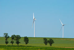Wind turbine. In a green landscape Stock Images
