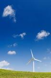 Wind turbine, green power, electricity generator. Single wind turbine on grassy field over deep blue sky, alternative energy, green power, electricity generator Stock Photos