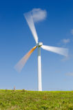 Wind turbine, green power, electricity generator. Single wind turbine on grassy field over deep blue sky, alternative energy, green power, electricity generator Stock Photos