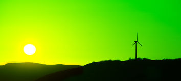 Wind Turbine at a green sunset. Silhoutte of a wind genator with green sky und yellow sun Stock Photos
