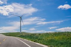 A Wind Turbine on the Highway and the Roadside under the Blue Sky and White Clouds stock photography
