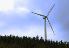 Wind turbine on hill with forest and blue sky Royalty Free Stock Images