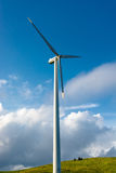 Wind turbine on hill in front of cloudy sky Royalty Free Stock Photo
