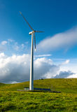 Wind turbine on hill in front of cloudy sky Royalty Free Stock Images